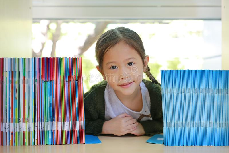 Happy little Asian child girl lying on bookshelf at library. Children creativity and imagination concept.  stock image