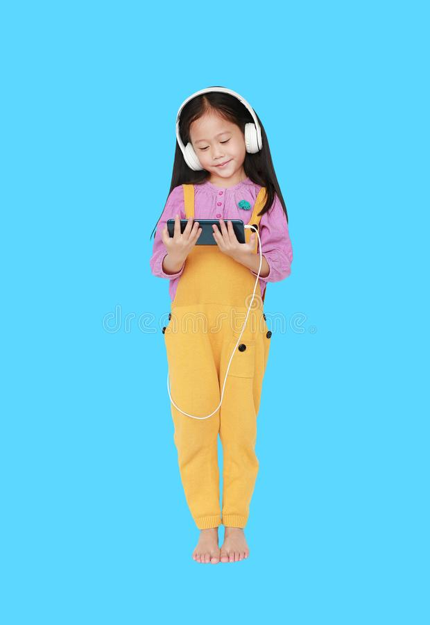Happy little Asian child girl in pink-yellow dungarees with headphones to enjoys listening music by smartphone isolated on cyan. Background. Full length in royalty free stock images