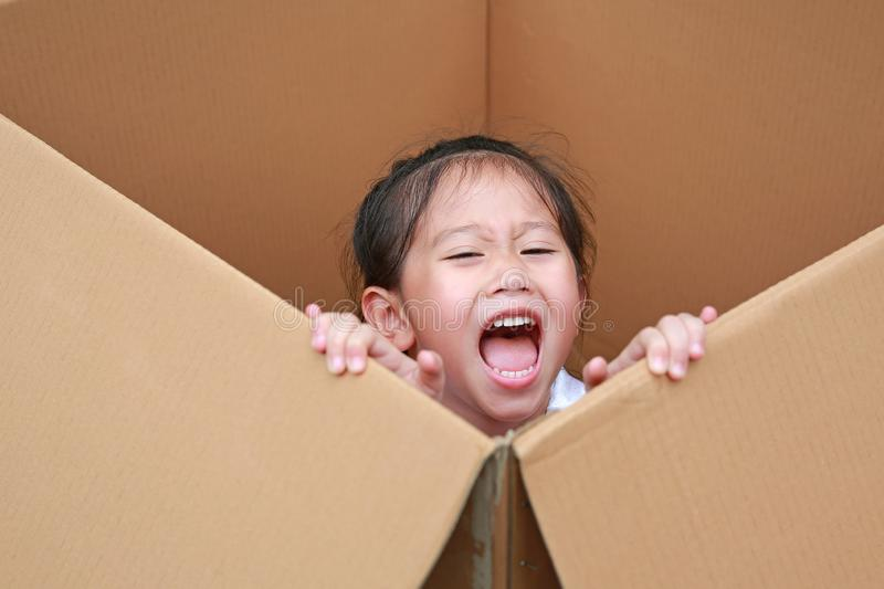 Happy little Asian child girl playing peekaboo and lie in big cardboard box royalty free stock images