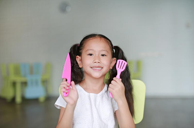 Happy little Asian child girl showing plastic knife and spade of frying pan in play room ready to cook learning royalty free stock photo