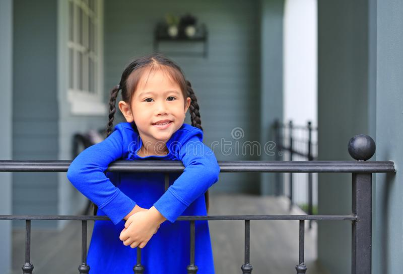 Happy little Asian child girl standing at house balcony bars and looking camera at the morning.  royalty free stock photos