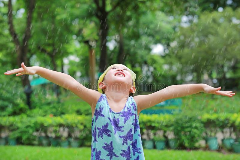 Happy little Asian child girl wearing emergency cap plastic bag on her head with open arms and enjoying rainfall in the green stock photos