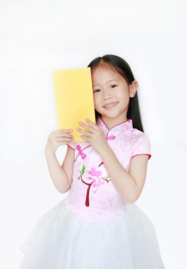 Happy little Asian child girl wearing pink traditional cheongsam dress smiling while receiving Chinese New Year gold envelope stock photography