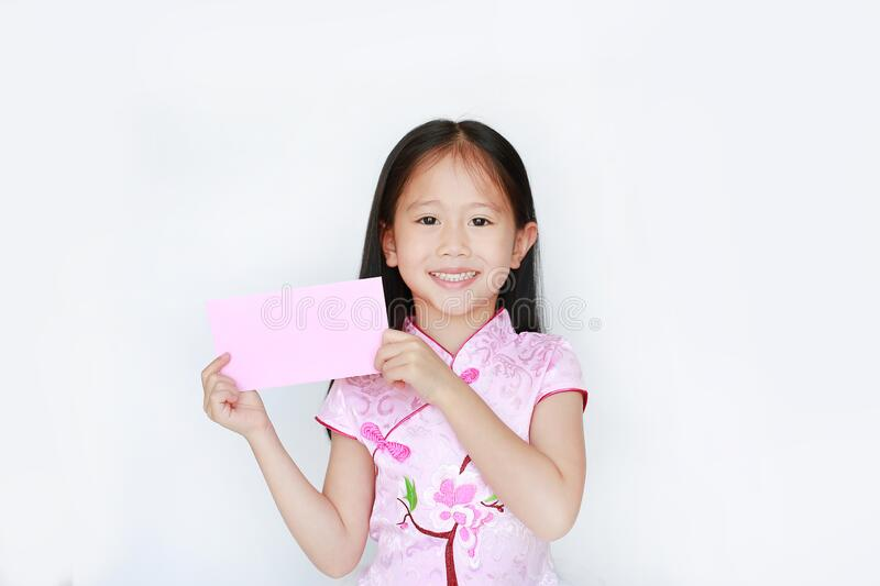 Happy little Asian child girl wearing pink traditional cheongsam dress smiling while receiving Chinese New Year pink envelope stock images