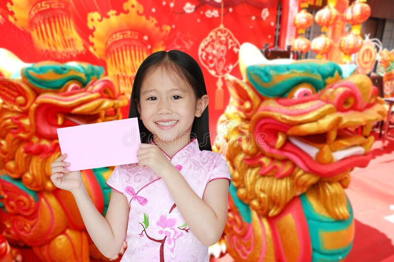 Happy little Asian child girl wearing pink traditional cheongsam dress smiling while receiving pink envelope packet on chinese stock photos