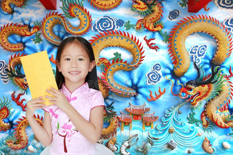 Happy little Asian child girl wearing pink traditional cheongsam dress smiling while receiving gold envelope packet on chinese stock photography