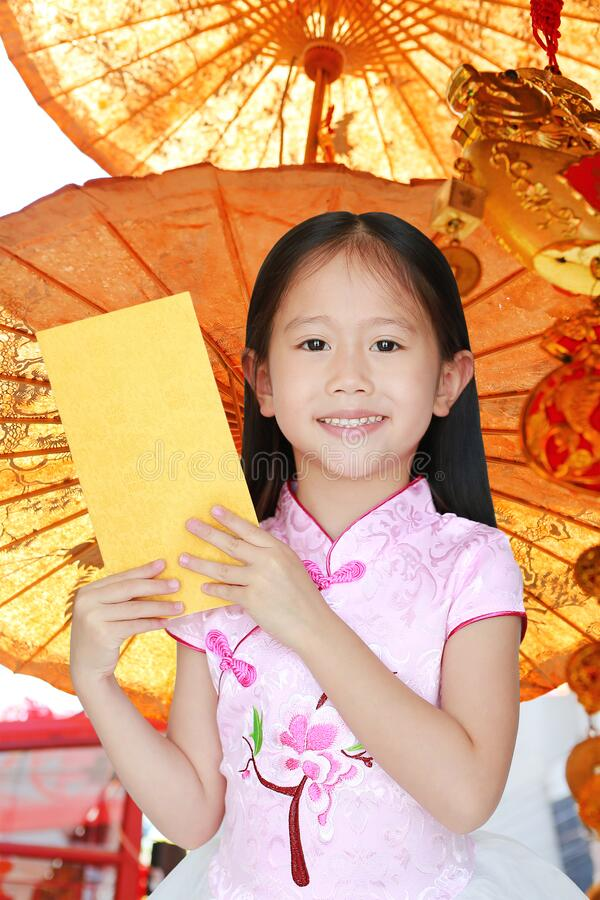 Happy little Asian child girl wearing pink traditional cheongsam dress smiling while receiving gold envelope packet on chinese royalty free stock image