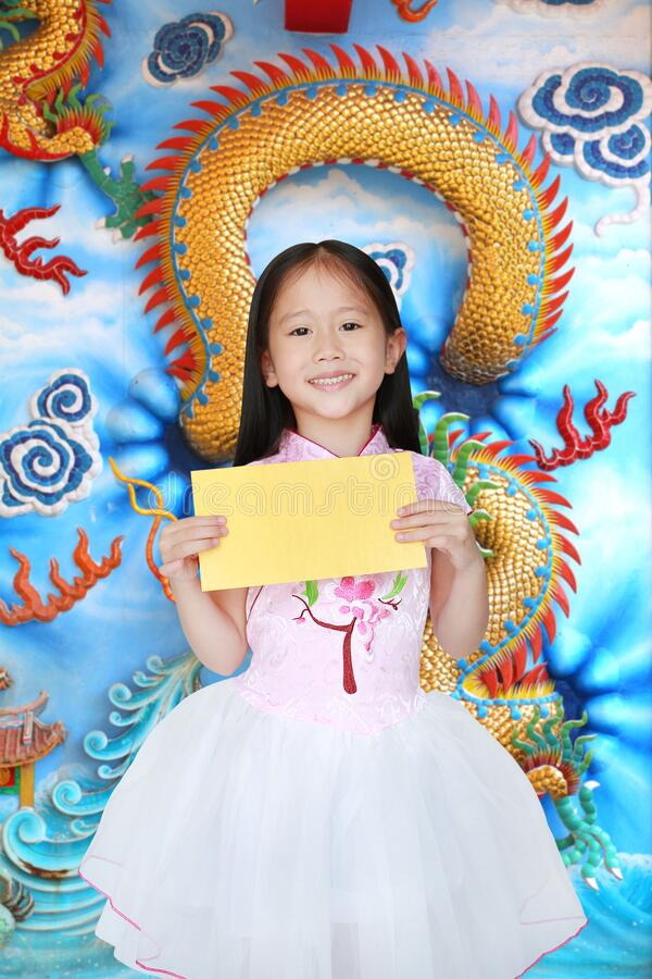 Happy little Asian child girl wearing pink traditional cheongsam dress smiling while receiving gold envelope packet on chinese royalty free stock images
