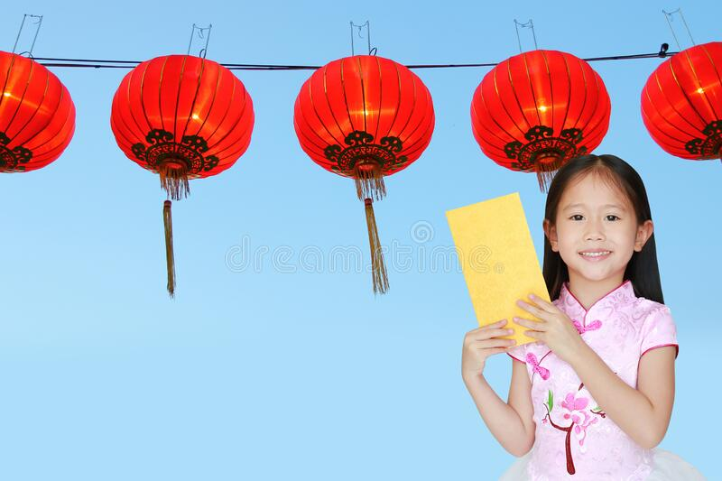 Happy little Asian child girl wearing pink traditional cheongsam dress smiling while receiving gold envelope packet on chinese red royalty free stock photos