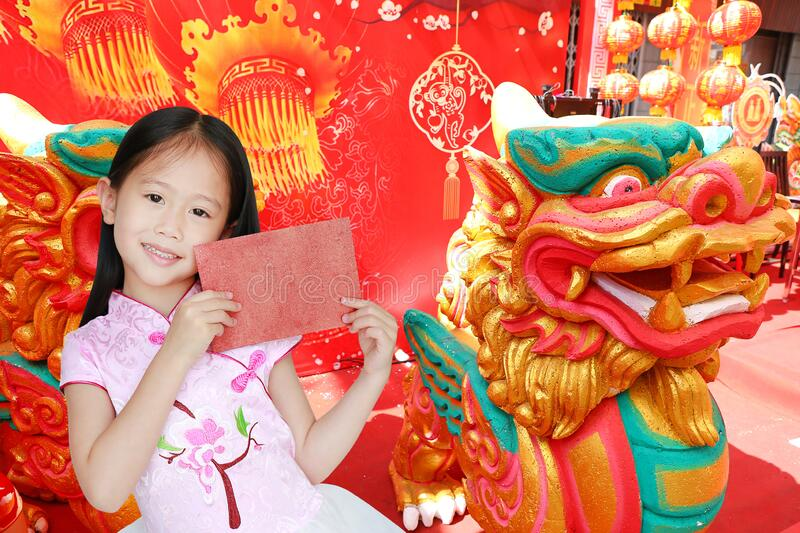 Happy little Asian child girl wearing pink traditional cheongsam dress smiling while receiving red envelope packet on chinese royalty free stock photo