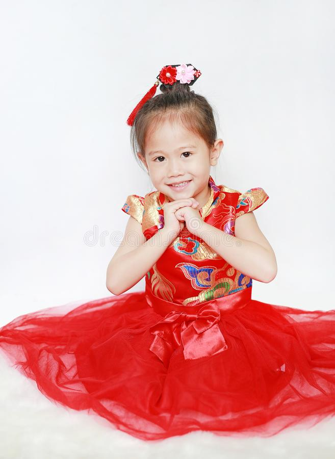 Happy little Asian child girl wearing red cheongsam with greeting gesture celebration for Chinese New Year isolated on white royalty free stock images