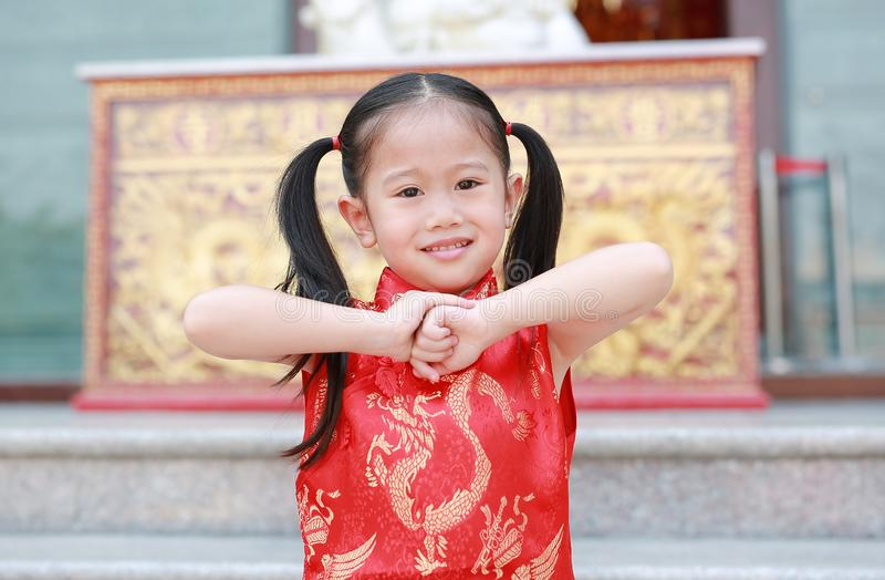 Happy little Asian child girl wearing red cheongsam with greeting gesture celebration for Chinese New Year at chinese temple in royalty free stock photo