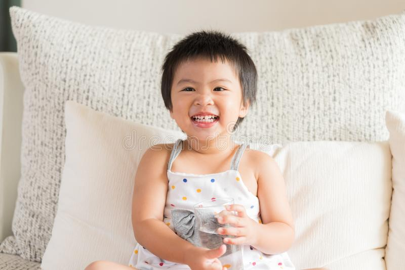 Happy little asian girl hand holding drinking water glass stock images