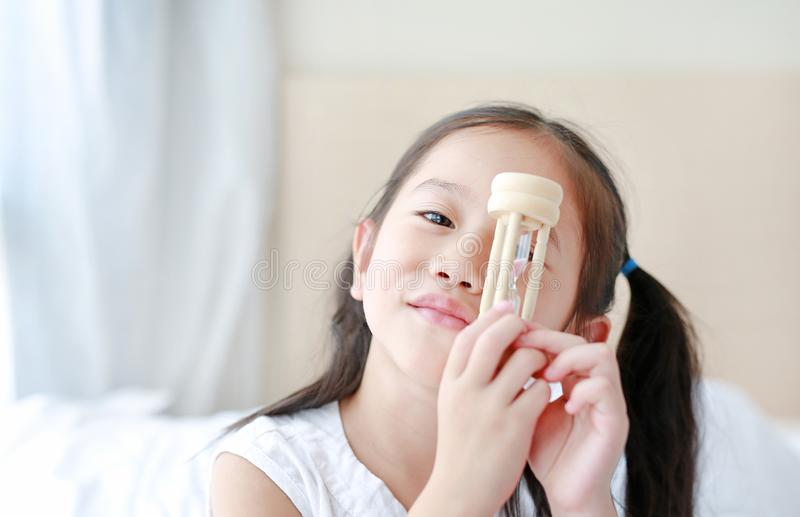 Happy little Asian girl holding sandglass in hand with looking through camera. Waiting times with hourglass royalty free stock photo