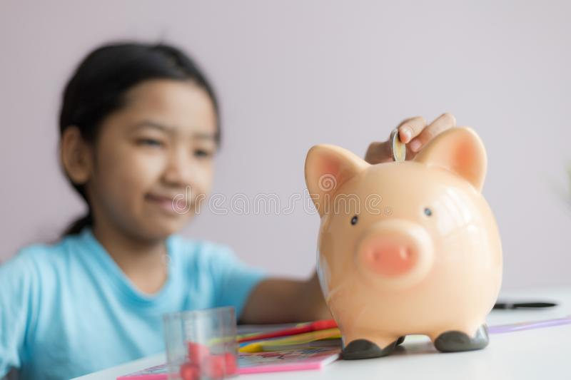 Happy little asian girl putting money coin into piggy bank select focus shallow depth of field. Finance, kid, child, person, cute, business, save, future stock photography