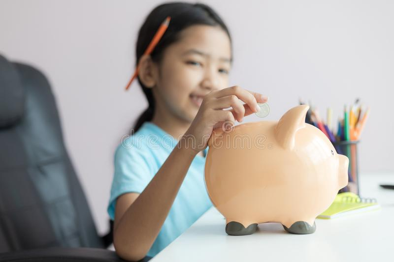 Happy little asian girl putting money coin into piggy bank select focus shallow depth of field. Finance, kid, child, person, cute, business, save, future royalty free stock images