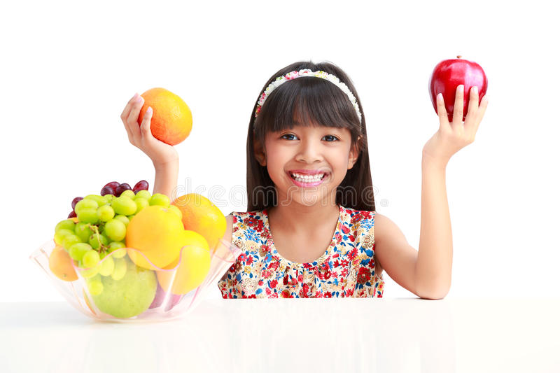 Download Happy Little Asian Girl Sitting On The Table With Plate Of Fruit Stock Photo - Image: 32280488
