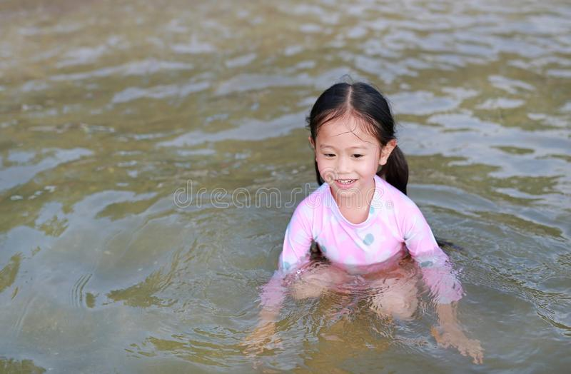 Happy little Asian girl in swimming suit playing water in a sea stock images
