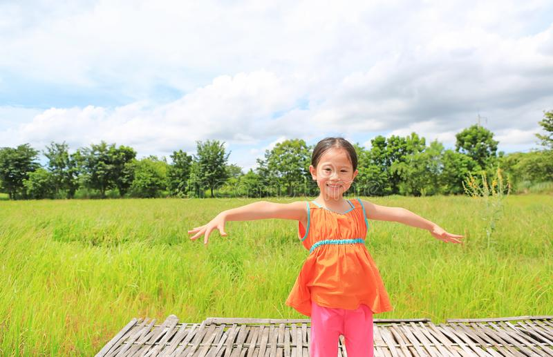 Happy little Asian kid girl stretch arms and relaxed at the young green paddy fields stock images