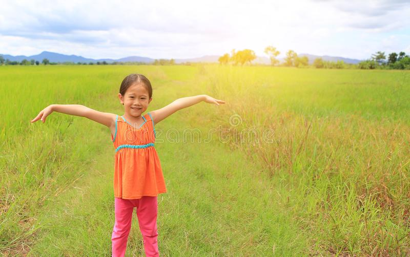 Happy little Asian kid girl stretch arms and relaxed at the young green paddy fields with mountain and cloud sky stock photography