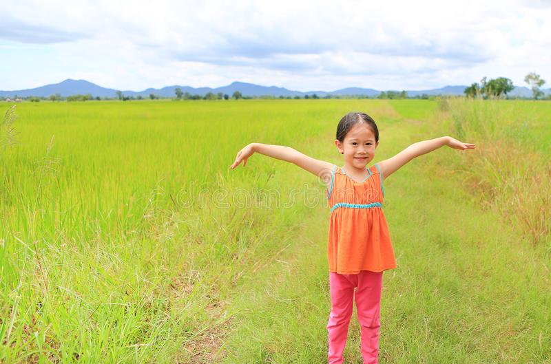 Happy little Asian kid girl stretch arms and relaxed at the young green paddy fields with mountain and cloud sky royalty free stock photo