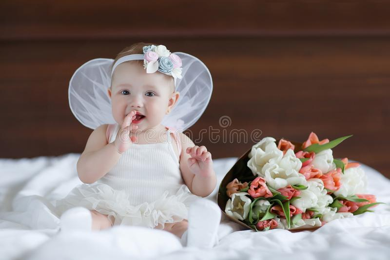 Happy little baby with angel wings. Blue-eyed baby with angel wings behind him.Baby Newborn with Angel Wings. Child Sitting at Blue Sky Cloud. Girl 5-7 months royalty free stock image