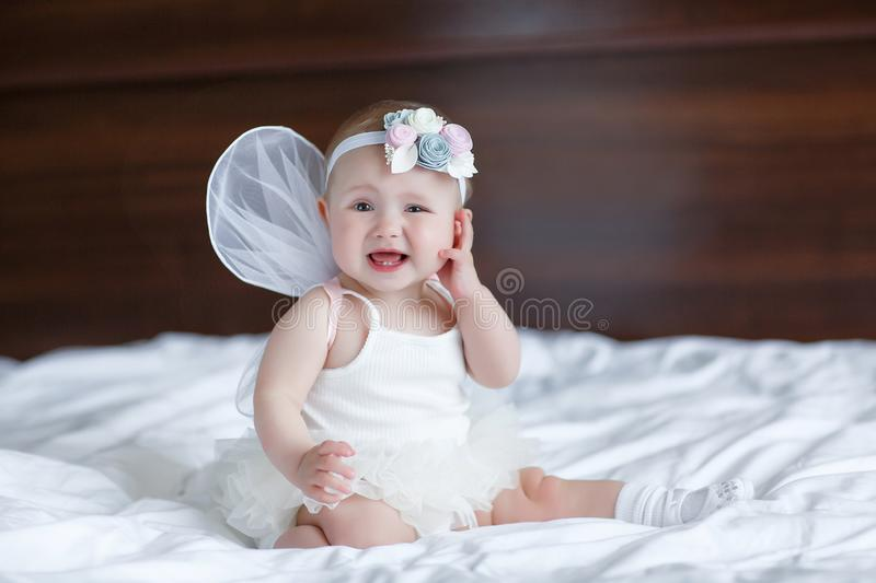 Happy little baby with angel wings. Blue-eyed baby with angel wings behind him.Baby Newborn with Angel Wings. Child Sitting at Blue Sky Cloud. Girl 5-7 months royalty free stock images