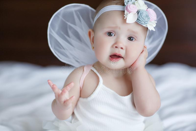 Happy little baby with angel wings. Blue-eyed baby with angel wings behind him.Baby Newborn with Angel Wings. Child Sitting at Blue Sky Cloud. Girl 5-7 months stock photos
