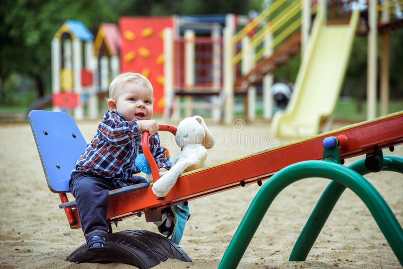 Happy little baby boy playing on the playground in the summer or autumn. Day royalty free stock photos