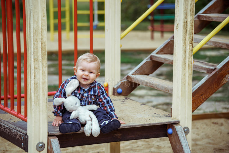 Happy little baby boy playing on the playground in the summer or autumn. Day royalty free stock photo