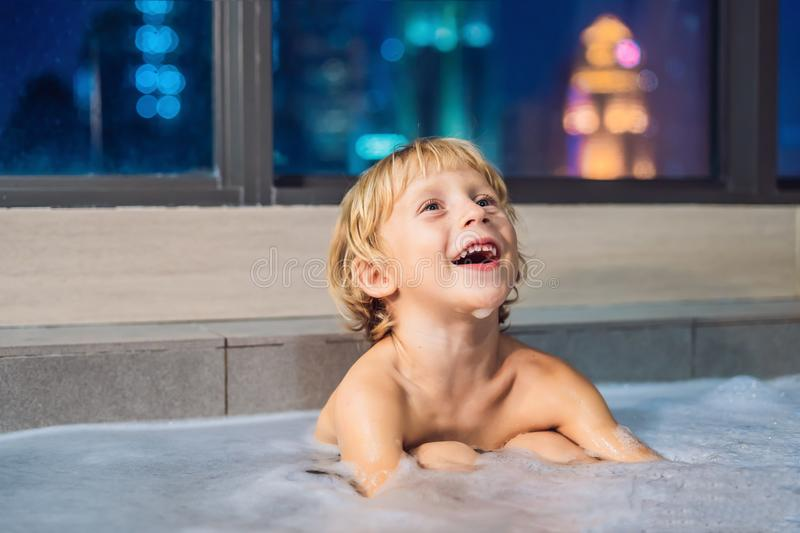 Happy little baby boy sitting in bath tub in the evening before royalty free stock photos