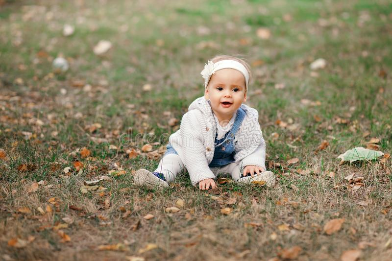 Happy little baby boy sitting on the grass in the park, garden, meadow. Baby looks at parents, beautiful warm weather royalty free stock photos