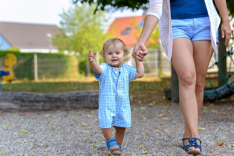 Happy little baby boy walking with his mother stock photos