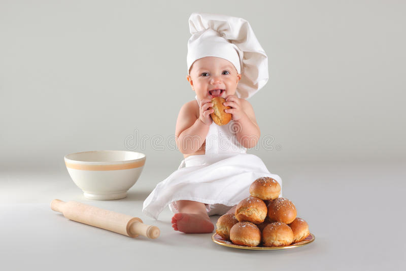Happy little baby in a cook cap laughs. Happy cute little baby in a cook cap laughs royalty free stock image