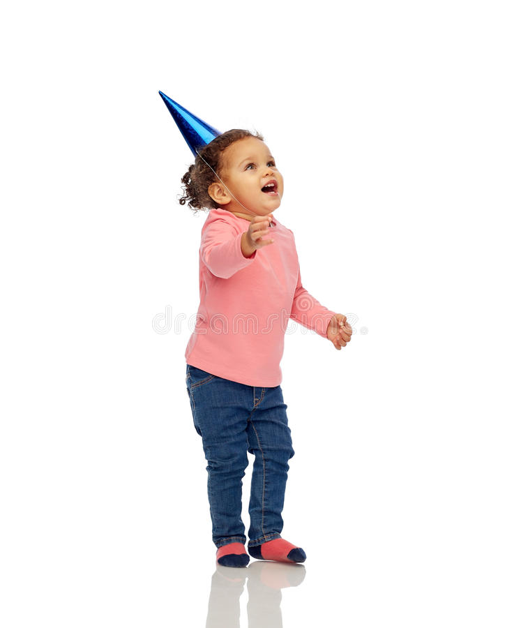 Happy little baby girl with birthday party hat. Childhood, fashion, birthday, holidays and people concept - happy smiling african american little baby girl with stock photos