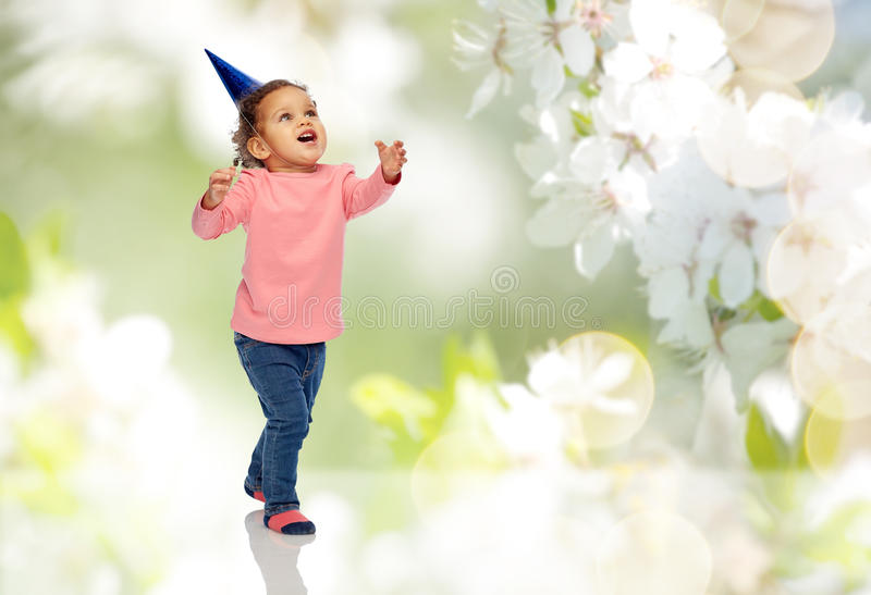 Happy little baby girl with birthday party hat. Childhood, fashion, birthday, holidays and people concept - happy smiling african american little baby girl with stock photo
