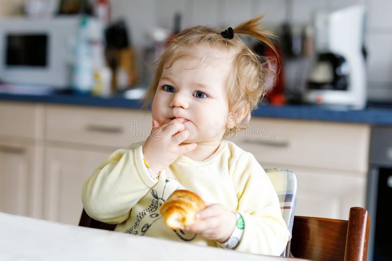 Happy little baby girl eating fresh croissant for breakfast or lunch. Healthy eating for children. Toddler child in colorful pajama sitting in domestic kitchen stock images