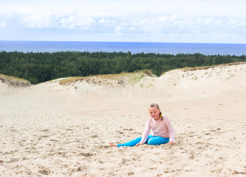 Happy little baby girl enjoys sand playing in the dunes royalty free stock photos