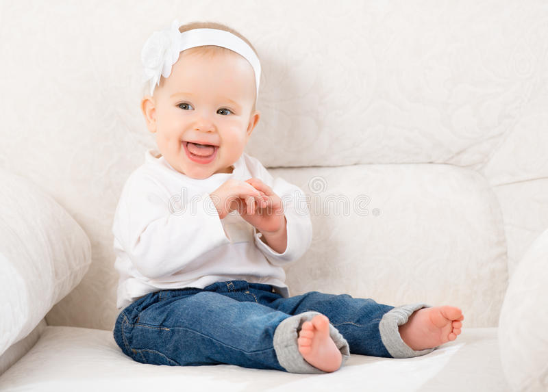Happy little baby girl laughing and sitting on a sofa in jeans. Happy little baby girl laughing and sitting on a white sofa in blue jeans stock photos