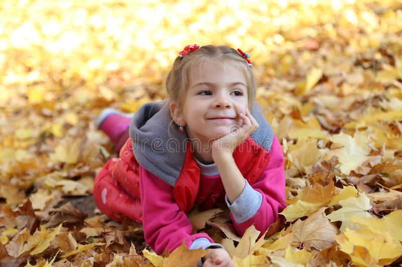 Happy little baby girl playing in autumn in yellow leaves stock photography