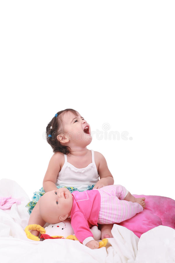Happy little baby girl sitting in the bed stock photos
