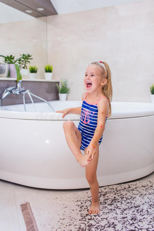 Happy little baby girl in a whetu blue swimsuit staying near bath tub in the bathroom and screaming with smile royalty free stock image