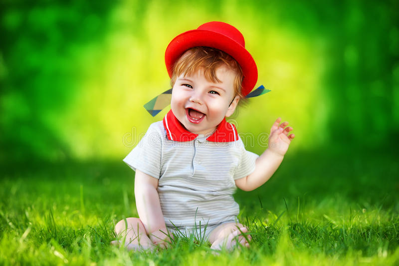 Happy little baby in red hat having fun in the park on solar glade. Summer vacations concept. The emotions. royalty free stock image