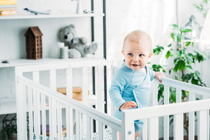 Happy little baby standing in crib. At home stock photography