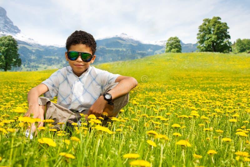 Happy little black sitting boy in sunglasses stock photos