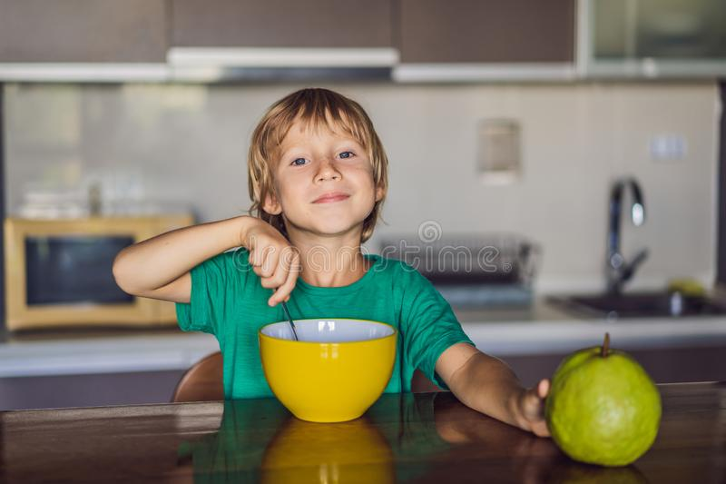 Happy little blond kid boy eating cereals for breakfast or lunch. Healthy eating for children. Child having breakfast stock photo