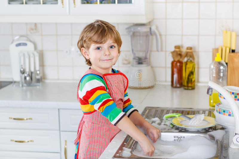 Happy little blond kid boy washing dishes in domestic kitchen. Happy little blond kid boy of 4 years washing dishes in domestic kitchen. Child having fun with stock photo
