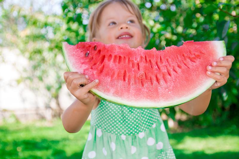 Happy little blonde girl with big slice watermelon royalty free stock photo