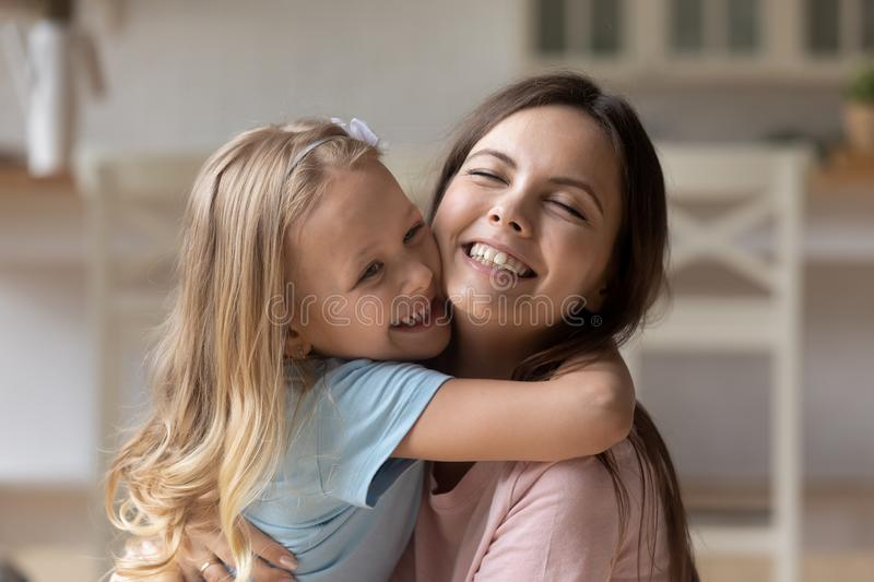 Happy little blonde girl hugging laughing mommy. stock photography