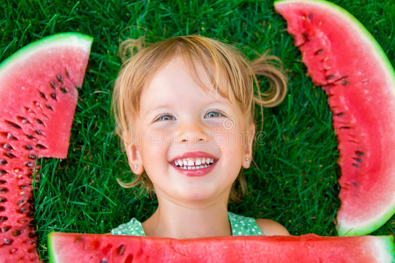 Happy little blonde girl lying on the grass with big slice watermelon in summer time. Smiling. Top view. Happy little blonde girl lying on the grass with big stock photo